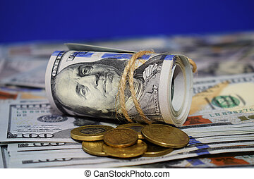 A roll of dollars on the background of scattered hundred dollar bills and various coins