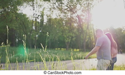 A romantic couple in a clearing among green trees in the rays of sunlight. They are walking around, holding hands. Summer. Love. Happy together. Only grass is in focus.