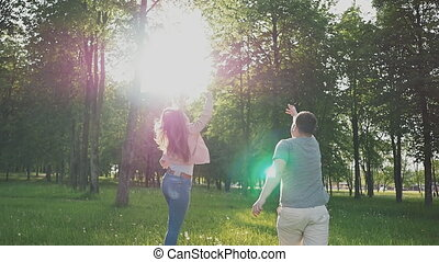 A romantic couple in a clearing among green trees in the rays of sunlight. They catch flying dandelions. Summer. Happy together.