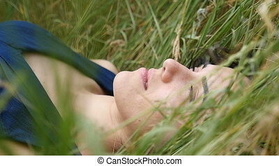 A romantic girl lies on a nice lawn and looks up dreamingly in slow motion