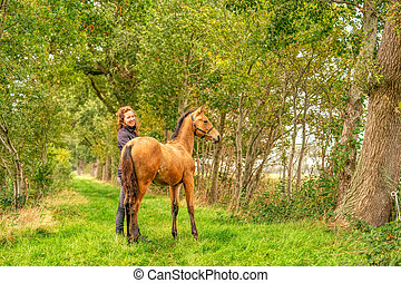 A romantic picture of a light brown foal, the female owner stands next to the stallion, autumn Sun. Selective focus