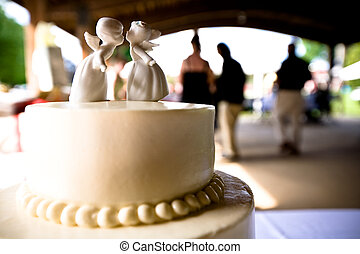 A romantic wedding cake topper, with out-of-focus guest dancing in the background.