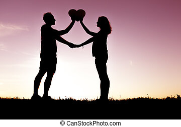 Romantic young couple holding heart shape on hands at sunset...