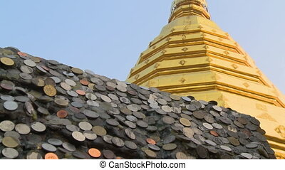 A hand held, low angle, close up shot of a roof covered with silver and copper coins.