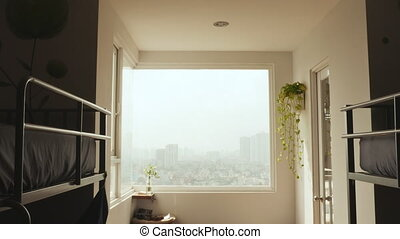 A room in a hostel with views of the city.