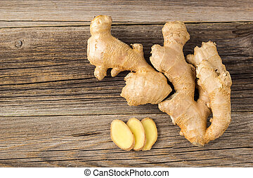 A root of ginger with sliced pieces on a wooden background