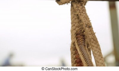 A rope tied to a metal bar - A hand held close up shot of a...