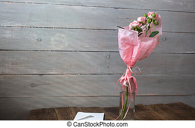a roses in a vase with envelope on wooden background