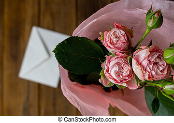 a roses in a vase with envelope on wooden grey background
