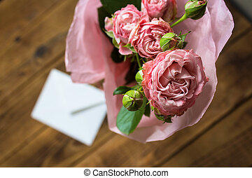a roses with envelope on wooden background