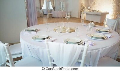 a round table in the foreground is a round table covered with a tablecloth and served with plates and glasses. Chiavari chairs stand around, the newlyweds presidium is visible in the background