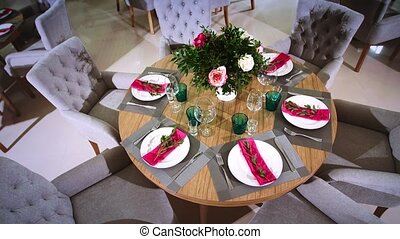 a round wooden table decorated with floral arrangements made from white plates with pink napkins around which there are soft chairs