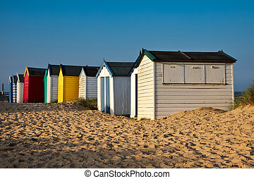A row of brightly coloured beach huts in Southwold Suffolk