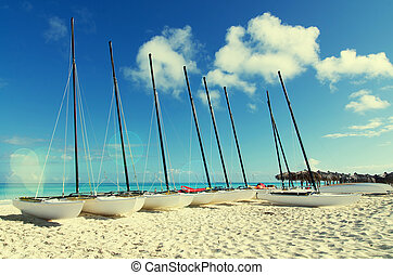 A row of catamarans on white sandy beach with retro effect