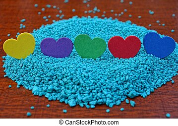 a row of colored hearts on blue sand on a red table