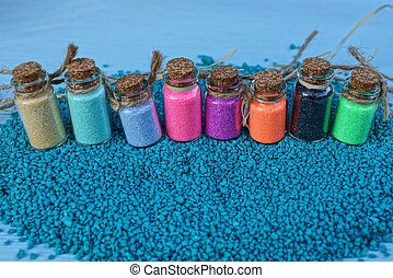 a row of glass bottles with colored sand