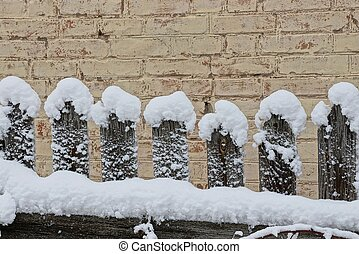 a row of gray wooden planks of an old fence in white snow on a winter street