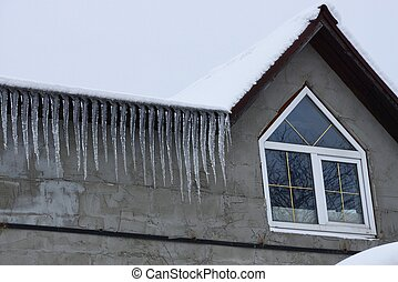 a row of icicles on the roof under white snow against a gray concrete wall with a window