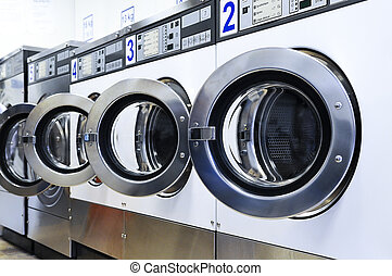 laundromat - A row of industrial washing machines in a ...