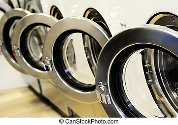 laundromat - A row of industrial washing machines in a...
