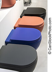 A row of new colored toilet bowls