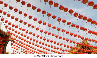 A row of red lanterns hanging off at a buddhist temple...