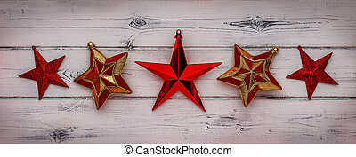 A row of red star christmas decorations on a distressed white wood