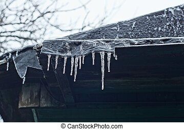 a row of white icicles on the black roof
