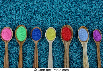 a row of wooden spoons with colored powder on blue stones