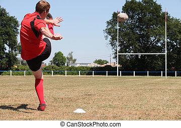 A rugby player kicking a ball