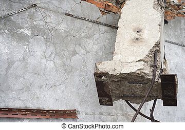 A ruined wall with grey mortar plaster and a huge concrete beam hanging from above. Background