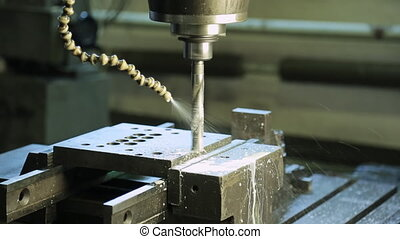 A running CNC machine with a rotating drill and a pipe for cutting fluid.
