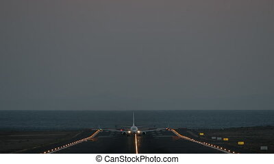 A frontal shot of an illuminated airstrip and a plane, that is riding to the camera and finally takes off