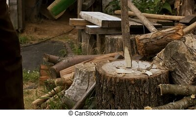 A rural man cuts wood with an axe and makes a peg for ...