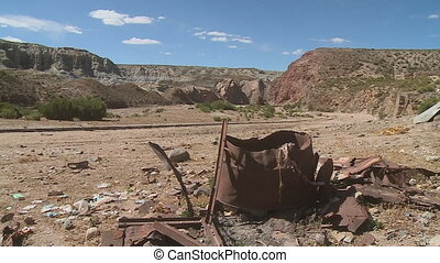 A rusted drum and metals with mountains at the background - ...