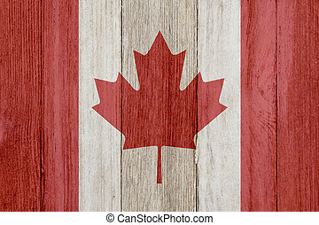 A rustic old Canadian flag on weathered wood