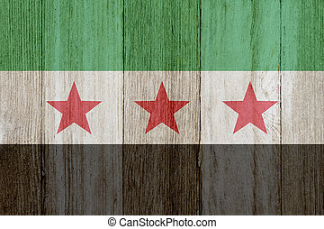 A rustic old Syrian flag on weathered wood