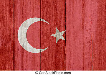 A rustic old Turkish flag on weathered wood