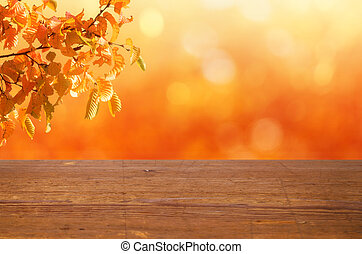 A rustic wooden table with an autumnal background