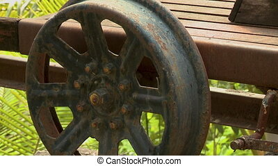 A rusty wheel of an old rail push trolley carriage - A ...