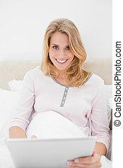 a, séance femme, dans lit, à, a, pc tablette, dans, main, regarder tout droit, et, sourire.