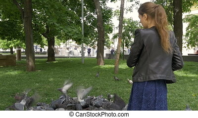 A sad beautiful girl is feeding pigeons in the park.