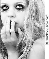 A sad blond girl with terrified expression