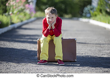 A sad boy sits on an old suitcase on the road. The child is about to leave.