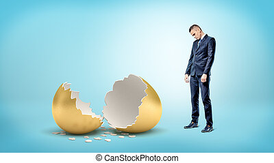 A sad businessman on blue background looks down on a giant broken golden egg.