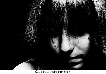 A sad girl looking down with her eyes unseen in black and white