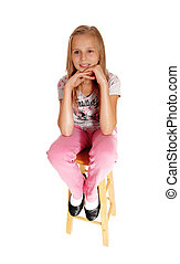 A sad looking young girl sitting on chair.