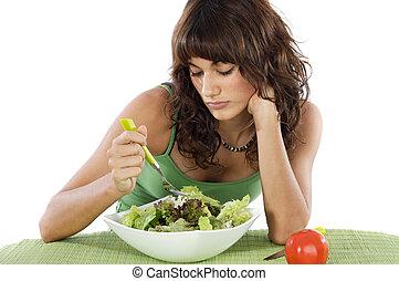 A sad teen eating salad
