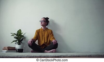 A sad young female student sitting on floor, having break...