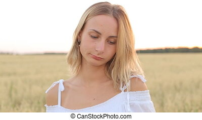 A sad young woman stands in a field and looks into the camera